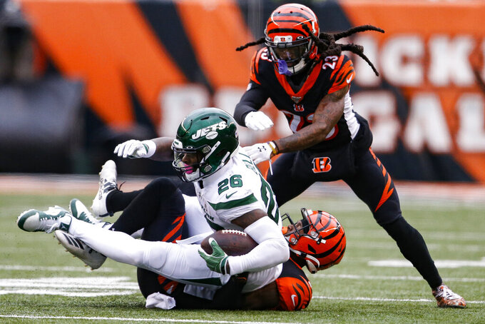 New York Jets running back Le'Veon Bell (26) is tackled by Cincinnati Bengals cornerback Darius Phillips, bottom, during the second half of an NFL football game, Sunday, Dec. 1, 2019, in Cincinnati. (AP Photo/Gary Landers)