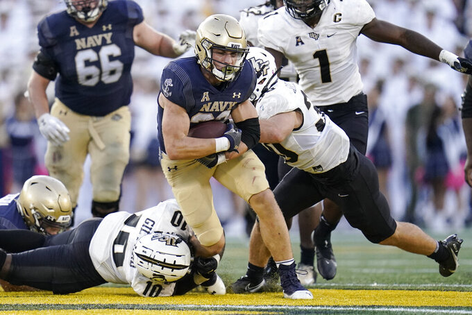 Navy fullback Isaac Ruoss, center, runs with the ball as UCF linebacker Eriq Gilyard (10) and linebacker Bryson Armstrong (30) try to bring him down during the second half of an NCAA college football game, Saturday, Oct. 2, 2021, in Annapolis, Md. Navy won 34-30. (AP Photo/Julio Cortez)