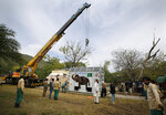Pakistani wildlife workers and experts from the international animal welfare organization Four Paws, use a crane to move a crate carrying an elephant named Kaavan before transporting him to a sanctuary in Cambodia, at the Marghazar Zoo in Islamabad, Pakistan, Sunday, Nov. 29, 2020. Kavaan, the world's loneliest elephant, who became a cause celebre in part because America's iconic singer and actress Cher joined the battle to save him from his desperate conditions at the zoo. (AP Photo/Anjum Naveed)