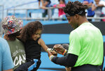 Carolina Panthers Cam Newton, right, signs an autograph during his charity kickball tournament in Charlotte, N.C., Friday, May 10, 2019. (AP Photo/Chuck Burton)