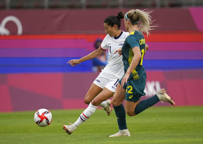 United States' Christen Press, left, is challenged by Australia's Ellie Carpenter during a women's soccer match at the 2020 Summer Olympics, Tuesday, July 27, 2021, in Kashima, Japan. (AP Photo/Fernando Vergara)