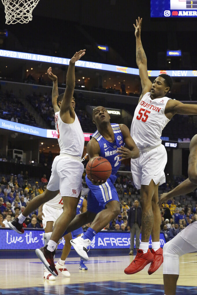 Memphis player Alex Lomax makes an attempt on goal under defense from Houston's Armani Brooks and Prison Gresham in the first half of an NCAA college basketball game at the American Athletic Conference tournament Saturday, March 16, 2019, in Memphis, Tenn. (AP Photo/Troy Glasgow)