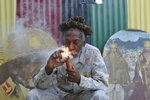 """FILE - In this Aug. 28, 2014 file photo, legalization advocate and reggae legend Bunny Wailer smokes a pipe stuffed with marijuana during a """"reasoning"""" session in a yard in Kingston, Jamaica. Wailer, a reggae luminary who was the last surviving original member of the legendary group The Wailers, died on Tuesday, March 2, 2021, in his native Jamaica, according to his manager. He was 73. (AP Photo/David McFadden, File)"""