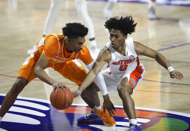 Florida guard Ques Glover (0) knocks the ball away from Tennessee guard Keon Johnson during the second half of an NCAA college basketball game Tuesday, Jan. 19. 2021, in Gainesville, Fla. (AP Photo/Matt Stamey)