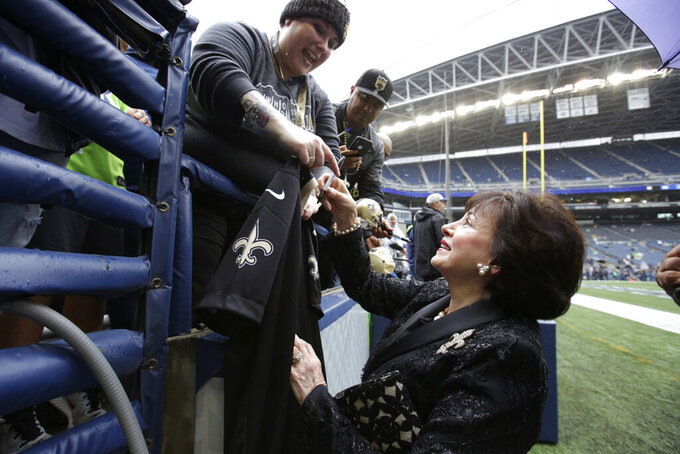 New Orleans Saints owner Gayle Benson, right, gives autographs to fans before an NFL football game against the Seattle Seahawks, Sunday, Sept. 22, 2019, in Seattle. (AP Photo/Scott Eklund)