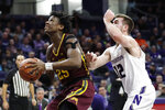 Minnesota center Daniel Oturu, left, drives to the basket past Northwestern guard Pat Spencer during the first half of an NCAA college basketball game in Evanston, Ill., Sunday, Feb. 23, 2020. (AP Photo/Nam Y. Huh)