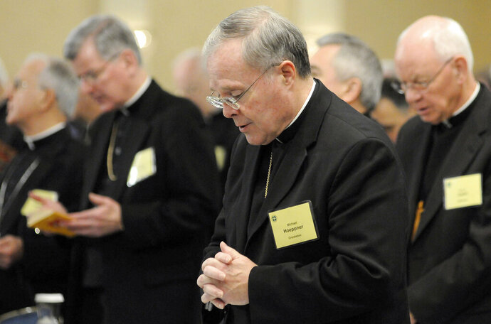 FILE - In this Nov. 10, 2008, Bishop Michael Hoeppner, center, of Crookston, Minn., prays during a semi-annual meeting of the United States Conference of Catholic Bishops in Baltimore. Hoeppner says he was trying to protect the confidentiality of a man who said he was sexually abused by a popular priest when he certified to other church officials that the priest was fit to work with children. Hoeppner of the Diocese of Crookston acknowledged in sworn testimony released Tuesday, Nov. 5, 2019, that he knew about sexual abuse allegations against the priest but was respecting the accuser's confidentiality. (AP Photo/ Steve Ruark, File)