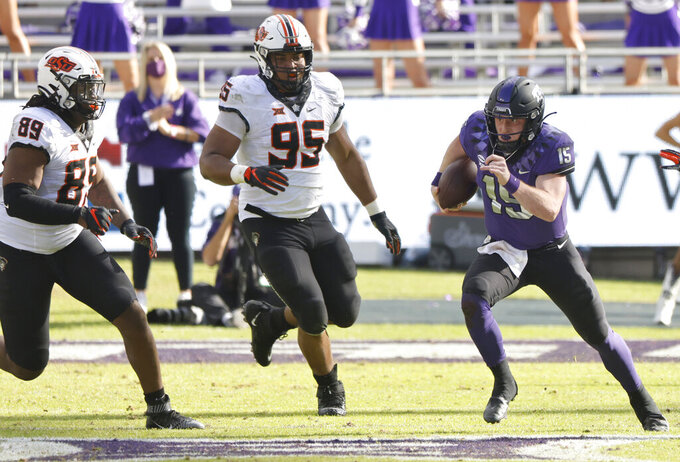 TCU quarterback Max Duggan (15) carries the ball as Oklahoma State defensive end Tyler Lacy (89) and Oklahoma State defensive tackle Israel Antwine (95) pursue during the second half of an NCAA college football game Saturday, Dec. 5, 2020, in Fort Worth, Texas. TCU won 29-22. (AP Photo/Ron Jenkins)