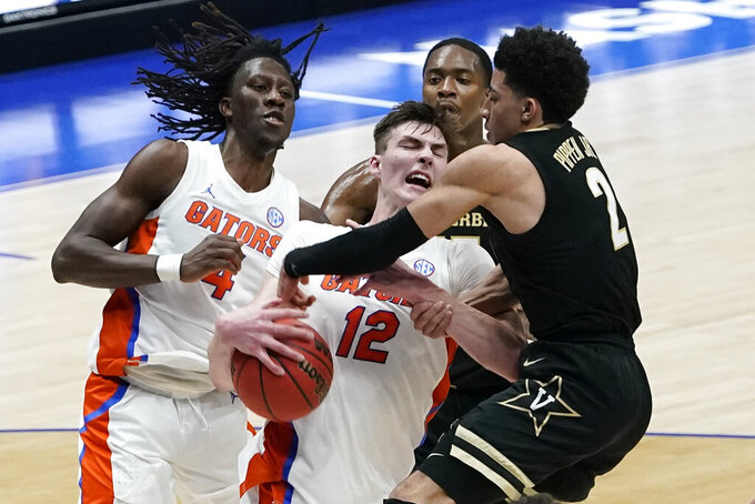 Vanderbilt's Trey Thomas (12) battles for the rebound with Vanderbilt's Scotty Pippen Jr. (2) in the second half of an NCAA college basketball game in the Southeastern Conference Tournament Thursday, March 11, 2021, in Nashville, Tenn. (AP Photo/Mark Humphrey)