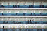 A passenger stands on the balcony of the cruise ship Diamond Princess anchored at the Yokohama Port in Yokohama, near Tokyo Friday, Feb. 7, 2020. Japan on Friday reported 41 new cases of a virus on a cruise ship that's been quarantined in Yokohama harbor while the death toll in mainland China rose to 636, including a doctor who got in trouble with authorities in the communist country for sounding an early warning about the disease threat. (AP Photo/Eugene Hoshiko)
