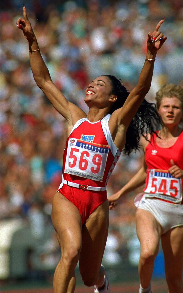 FILE - In this Sept. 25, 1988, file photo, Florence Griffith-Joyner celebrates her victory in the 100-meter dash at the 1988 Olympic Games in Seoul, South Korea. She was clocked at 10.54 seconds, to break an Olympic record. Behind her is Natalia Pomoshchnikova of the Soviet Union, who finished sixth in the race. (AP Photo/Dieter Endlicher, File)