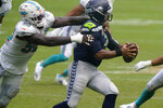 Miami Dolphins defensive end Shaq Lawson (90) sacks Seattle Seahawks quarterback Russell Wilson (3), during the second half of an NFL football game, Sunday, Oct. 4, 2020, in Miami Gardens, Fla. (AP Photo/Lynne Sladky)