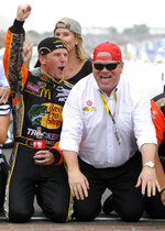 """FILE - Jamie McMurray, left, and car owner Chip Ganassi celebrate on the start-finish line after McMurray won the NASCAR Brickyard 400 auto race at Indianapolis Motor Speedway in Indianapolis, in this Sunday, July 25, 2010, file photo. Chip Ganassi has sold his NASCAR team to Justin Marks, owner of Trackhouse Racing, and will pull out of the nation's top stock car series at the end of this season. Ganassi fields two cars in the Cup Series but will transfer his North Carolina race shop and all its assets to Marks for 2022. """"He made me a great offer that required my attention,"""" Ganassi told The Associated Press on Wednesday, June 30, 3031, as the sale was announced. (AP Photo/Tom Strickland, File)"""