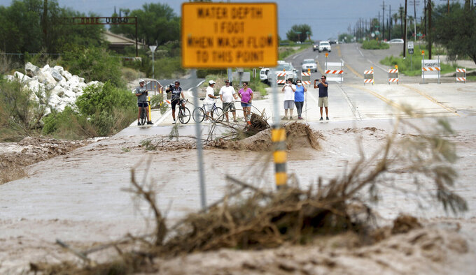 The flooded Pantano Wash in Tucson, Ariz., draws crowds of onlookers where it forced closure of Harrison Road following a night of intense storms and heavy rain, Friday, July 23, 2021. (Kelly Presnell/Arizona Daily Star via AP)