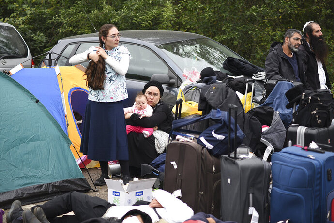 Jewish pilgrims gather on the Belarus-Ukraine border, in Belarus, Tuesday, Sept. 15, 2020. About 700 Jewish pilgrims are stuck on Belarus' border due to coroavirus restrictions that bar them from entering Ukraine. Thousands of pilgrims visit the city each September for Rosh Hashana, the Jewish new year. However, Ukraine closed its borders in late August amid a surge in COVID-19 infections. (TUT.by via AP)