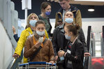 People wearing face masks to protect against coronavirus infection leave a mall in St.Petersburg, Russia, Friday, Sept. 11, 2020. Russia has seen an uptick in new cases of coronavirus in recent weeks and hospitalizations have started to increase. (AP Photo/Dmitri Lovetsky)