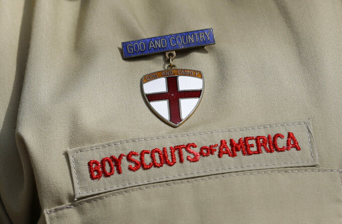 FILE - This Feb. 4, 2013 file photo shows a close up of a Boy Scout uniform in Irving, Texas. Amid the Boy Scouts of America's complex bankruptcy case filed in February 2020, there is worsening friction between the BSA and the major religious groups that help it run thousands of Scout units. At issue: the churches' fears that an eventual settlement – while protecting the BSA from future sex-abuse lawsuits – could leave many churches unprotected. (AP Photo/Tony Gutierrez, File)