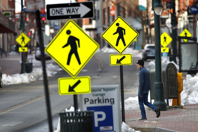 Crosswalk signs outnumber the pedestrians in downtown Portland, Maine, just hours before a stay-at-home order goes into effect Wednesday, March 25, 2020, that will close all but essential workplaces in the city. City officials say residents must shelter in place starting at 5 p.m. Wednesday to help slow the spread of the coronavirus. Maine has reached 118 coronavirus cases, the majority in Cumberland and York counties. (AP Photo/Robert F. Bukaty)