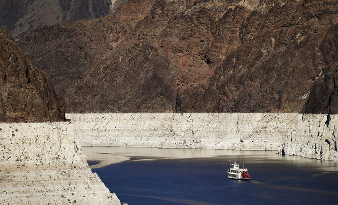 FILE - In this Oct. 14, 2015, file photo, a riverboat glides through Lake Mead on the Colorado River at Hoover Dam near Boulder City, Nev. Despite drought, cities in the U.S. West expect their populations to grow considerably in the coming decades. From Phoenix to Boise, officials are working to ensure they have the resources, infrastructure and housing supply to meet growth projections. In certain parts of the region, their efforts are constrained by the fact that sprawling metro areas are surrounded by land owned by the federal government. U.S. Sen. Catherine Cortez Masto wants to remedy the issue in Las Vegas by strengthening protections for some public lands while approving the sale of others to commercial and residential developers. (AP Photo/Jae C. Hong, File)