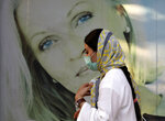 A woman wearing protective face mask to help prevent the spread of the coronavirus walks past an advertisement of skin care products in southern Tehran, Iran, Tuesday, July 20, 2021. Iran on Tuesday broke another record in the country's daily new coronavirus cases, even as Tehran and its surroundings went into lockdown, a week-long measure imposed amid another surge in the pandemic. (AP Photo/Vahid Salemi)