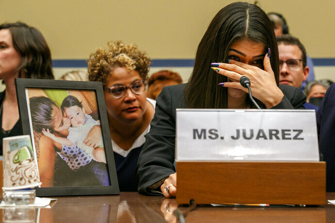 Yazmin Juárez, reacts as a photos of her daughter, Mariee, 1, who died after being released from detention by U.S. Immigration and Customs Enforcement, is placed next to her at a House Oversight subcommittee hearing on Civil Rights and Civil Liberties to discuss treatment of immigrant children at the southern border, Wednesday, July 10, 2019, on Capitol Hill in Washington. (AP Photo/Jacquelyn Martin)