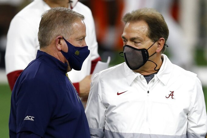 Notre Dame head coach Brian Kelly, left, and Alabama head coach Nick Saban, right, greet each other before their Rose Bowl NCAA college football game in Arlington, Texas, Friday, Jan. 1, 2021. (AP Photo/Roger Steinman)