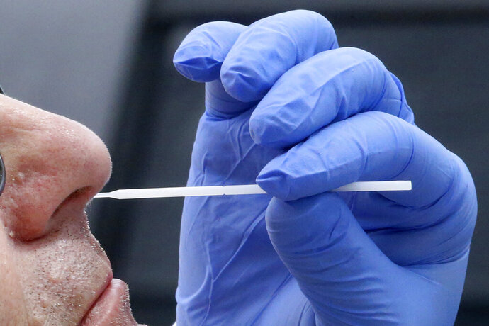 FILE - In this Friday, June 12, 2020 file photo, a nurse uses a swab to perform a coronavirus test in Salt Lake City. On Friday, July 10, 2020, The Associated Press reported on stories circulating online incorrectly asserting that the nasal swab test commonly used for diagnosing COVID-19 involves obtaining a sample from a protective layer of cells known as the blood-brain barrier, which can result in inflammation of the brain. The swab goes so far back into the nose that it can be uncomfortable, even causing some people's eyes to water. But it doesn't touch the area where blood vessels and the brain exchange important nutrients. (AP Photo/Rick Bowmer)