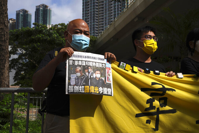 Pro-democracy activists holding a copy of Apple Daily newspaper and banner protest outside a court in Hong Kong, Saturday, June 19, 2021, to demand to release political prisoners. The top editor of the Hong Kong's pro-democracy newspaper and the head of its parent company were brought to a courthouse Saturday for their first hearing since their arrest under the city's national security law.(AP Photo/Kin Cheung)