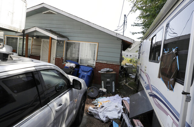 FILE - In this July 31, 2019, file photo, vehicles are parked outside the home of Paige A. Thompson, who uses the online handle