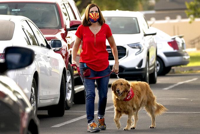 U.S. Sen. Martha McSally, R-Ariz., walks her dog Boomer to greet voters at a polling station early, Tuesday, Nov. 3, 2020, in Mesa, Ariz. (AP Photo/Matt York)