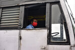A driver wearing a mask parks his bus after a special trip for government employees during extended lockdown in Kochi, southern Kerala state, India, Monday, May 18, 2020. India on Monday saw a slow trickle of people returning outdoors and thin traffic on its roads in some states, a day after the federal government extended the nationwide coronavirus lockdown to May 31 but eased many restrictions to restore economic activity. (AP Photo/R S Iyer)