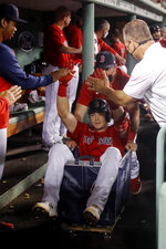 Boston Red Sox's Bobby Dalbec gets a ride in the laundry cart after hitting his second home run of the night during the ninth inning of the team's baseball game against the Tampa Bay Rays on Tuesday, Sept. 7, 2021, at Fenway Park in Boston. (AP Photo/Winslow Townson)