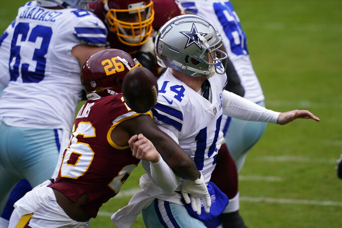 Washington Football Team strong safety Landon Collins (26) knocks the ball of the hands of Dallas Cowboys quarterback Andy Dalton (14) during the first half of an NFL football game, Sunday, Oct. 25, 2020, in Landover, Md. (AP Photo/Susan Walsh)