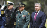 Colombia's Interim Defense Minister and Armed Forces Commander Gen. Luis Fernando Navarro, center, and Colombia's President Ivan Duque, right, attend a graduation ceremony for police cadets in Bogota, Colombia, Thursday, Nov. 7, 2019. Colombia's Defense Minister Guillermo Botero resigned Wednesday after a lawmaker accused him of failing to disclose that eight minors had been killed in a military operation against dissident rebels. (AP Photo/Fernando Vergara)