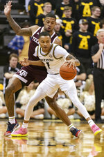 Missouri guard Xavier Pinson, bottom, dribbles around Texas A&M guard Savion Flagg, top, during the first half of an NCAA college basketball game Tuesday, Jan. 21, 2020, in Columbia, Mo. (AP Photo/L.G. Patterson)
