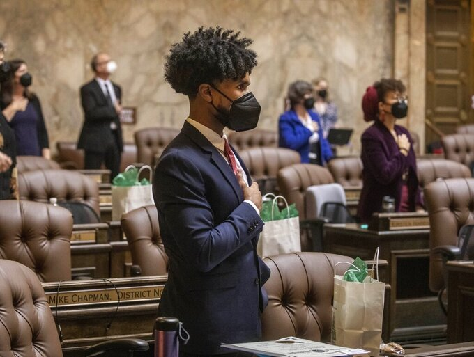 FILE - In this Jan. 11, 2021, file photo, Rep. Jesse Johnson, D-Federal Way, stands with other members at the beginning of the House session, where legislators were spaced at a social distance, in Olympia, Wash. Johnson hopes to see the Legislature end qualified immunity for police officers, which would allow them to be sued in state court, and to see it authorize community oversight boards that could have input on local policies and receive complaints about officers. (Steve Ringman/The Seattle Times via AP, Pool, File)