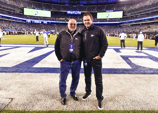 In this 2019 photo provided by XTECH, XTECH co-founders Teddy Monica, left, and and Bob Broderick pose in MetLife Stadium in East Rutherford, N.J. Broderick and Monica have found ways to get shoulder pads out to NFL, college and high school players in the midst of the coronavirus pandemic. (Evan Pinkus/XTECH via AP)
