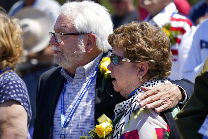 Monica Young is comforted by her husband, Richard Young, while attending the unveiling of a monument to honor the military passengers of Flying Tiger Line Flight 739, Saturday, May 15, 2021, in Columbia Falls, Maine. Monica's father, SFC John Wendall, was among those killed on the secret mission to Vietnam in 1962. (AP Photo/Robert F. Bukaty)