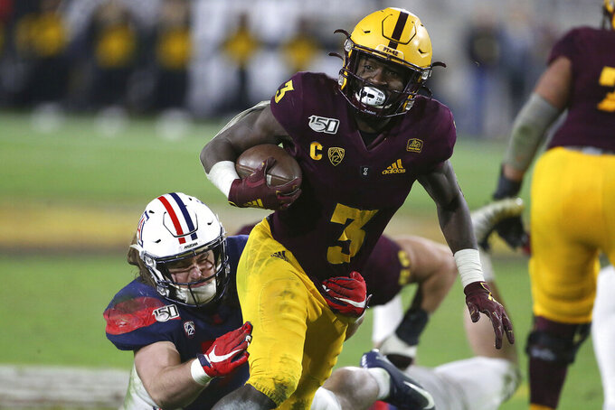 FILE - In this Nov. 30, 2019, file photo, Arizona State's Eno Benjamin (3) slips the tackle of Arizona's Colin Schooler (7) during the second half of an NCAA college football game in Tempe, Ariz. Five NFL prospects, including Benjamin, are being featured in a Panini docu-series that chronicles their paths to the NFL. With the coronavirus outbreak, teams were not allowed to visit with prospects. These five players get to tell their stories, giving them an advantage over the rest of the field. (AP Photo/Darryl Webb, File)