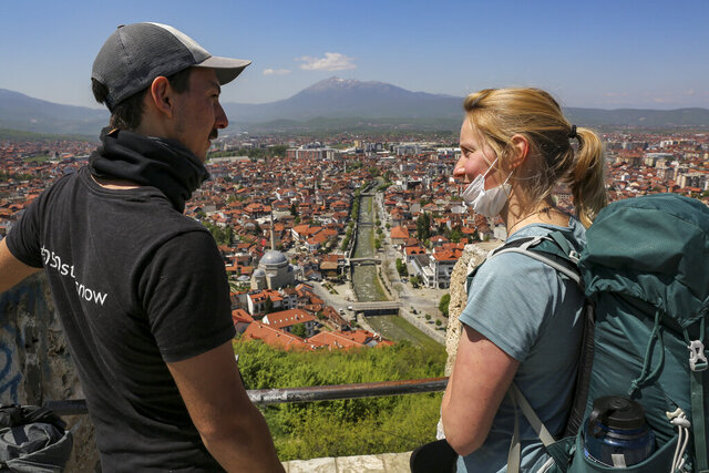 In this photo taken on Friday, April 24, 2020, Rosie Watson and Mike Elm  visit the medieval fortress in Prizren, Kosovo. British climate activists Rosie Watson and Mike Elm were on an international bicycle and running tour to promote their campaign when they got stuck in Kosovo because of the coronavirus pandemic. Watson, 25, from Loweswater in northwestern England, and Mike Elm, 32, from Edinburgh, Scotland, have been stranded in Prizren, a town in Kosovo, 85 kilometers (50 miles) southwest of the capital Pristina. Since mid-March, Kosovo has been in a lockdown with all of its land and air border crossings shut. The virus has killed at least 22 people and there are more than 780 confirmed cases. (AP Photo/Visar Kryeziu)