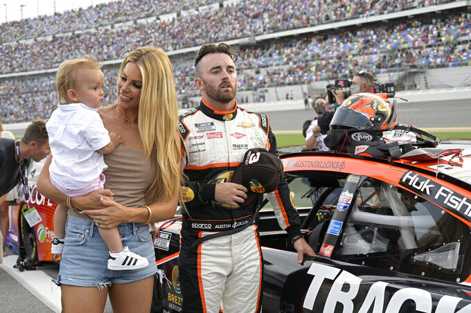 Austin Dillon stands next to his vehicle with his wife Whitney Dillon and son, Ace, on pit road before a NASCAR Cup Series auto race at Daytona International Speedway, Saturday, Aug. 28, 2021, in Daytona Beach, Fla. (AP Photo/Phelan M. Ebenhack)