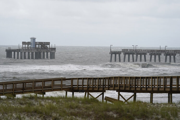 Waves move near a damaged pier at Gulf State Park after Hurricane Sally moved through, Wednesday, Sept. 16, 2020, in Gulf Shores, Ala. The hurricane made landfall Wednesday near Gulf Shores, Alabama, as a Category 2 storm, pushing a surge of ocean water onto the coast and dumping torrential rain that forecasters said would cause dangerous flooding from the Florida Panhandle to Mississippi and well inland in the days ahead.(AP Photo/Gerald Herbert)