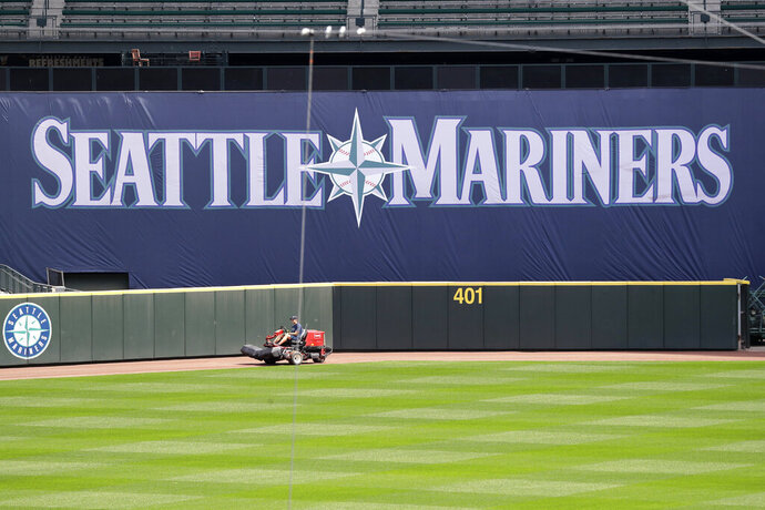 In an otherwise empty ballpark, a grounds crew member continues to keep the Seattle Mariners' field in playing shape as the ballpark goes into its seventh week without baseball played because of the coronavirus outbreak Monday, May 11, 2020, in Seattle. A person familiar with the decision tells The Associated Press that Major League Baseball owners have given the go-ahead to making a proposal to the players' union that could lead to the coronavirus-delayed season starting around the Fourth of July weekend in ballparks without fans. (AP Photo/Elaine Thompson)