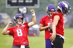 Minnesota Vikings quarterback Kirk Cousins (8) responds to the crowd, next to quarterbacks Nate Stanley (14) and Kellen Mond (11) during NFL football training camp Friday, July 30, 2021, in Eagan, Minn. (AP Photo/Bruce Kluckhohn)