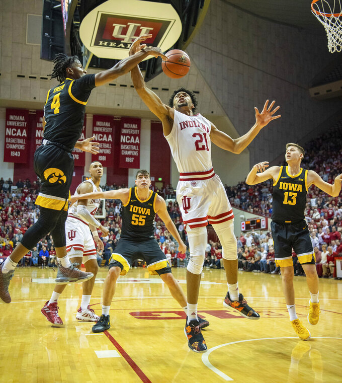 Iowa guard Bakari Evelyn (4), left, swats the ball away from Indiana forward Jerome Hunter (21) who drives to the basket during the first half of an NCAA college basketball game, Thursday, Feb. 13, 2020, in Bloomington, Ind. (AP Photo/Doug McSchooler)