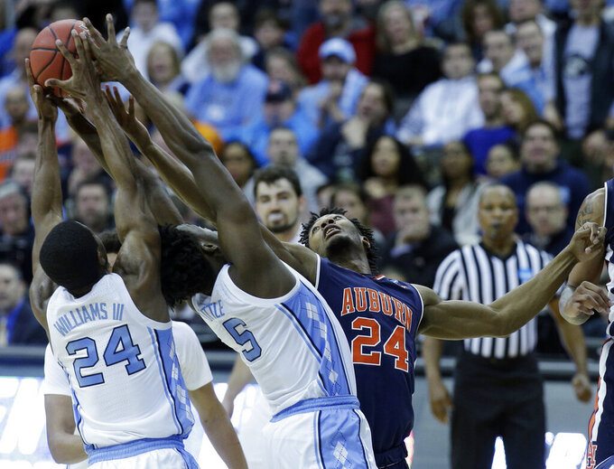 Auburn's Anfernee McLemore, right, reaches for a rebound along with North Carolina's Kenny Williams, left, and Nassir Little during the first half of a men's NCAA tournament college basketball Midwest Regional semifinal game Friday, March 29, 2019, in Kansas City, Mo. (AP Photo/Charlie Riedel)