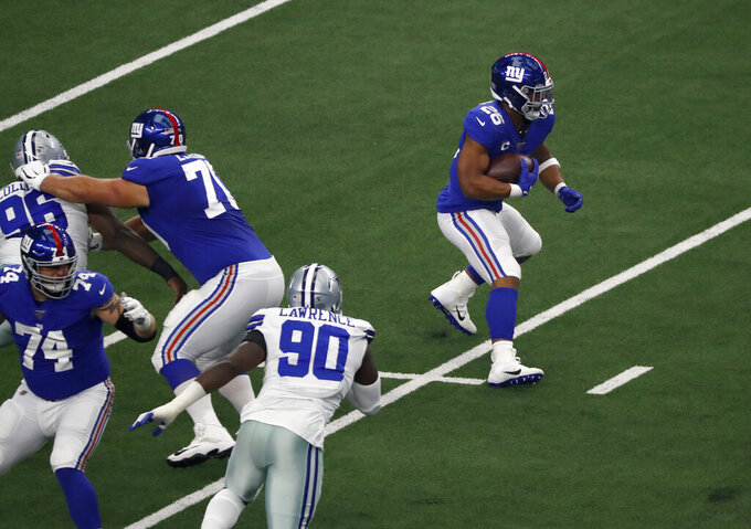 Dallas Cowboys defensive end Demarcus Lawrence (90) gives pursuit as New York Giants running back Saquon Barkley (26) runs the ball in the first half of a NFL football game in Arlington, Texas, Sunday, Sept. 8, 2019. (AP Photo/Roger Steinman)