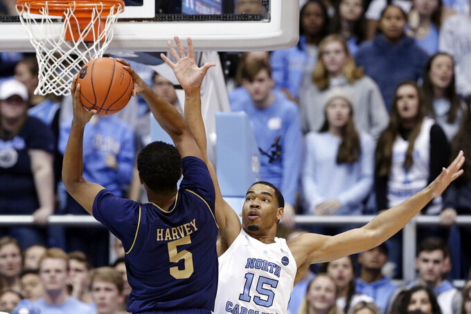 North Carolina's Garrison Brooks (15) defends as Notre Dame's D.J. Harvey (5) shoots during the first half of an NCAA college basketball game in Chapel Hill, N.C., Tuesday, Jan. 15, 2019. (AP Photo/Gerry Broome)