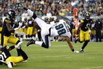 Philadelphia Eagles' Dallas Goedert (88) is sent flying on a tackle by Pittsburgh Steelers' Nat Berhe (31) and Farrington Huguenin (41) during the first half of a preseason NFL football game Thursday, Aug. 9, 2018, in Philadelphia. (AP Photo/Michael Perez)