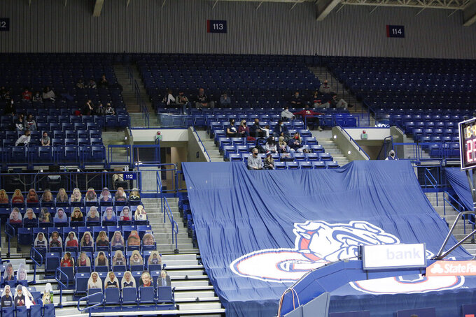 Players' families, top, the first fans allowed to watch a game at the McCarthey Athletic Center this season due to the COVID-19 pandemic, watch the first half of an NCAA college basketball game between Gonzaga and Saint Mary's in Spokane, Wash., Thursday, Feb. 18, 2021. (AP Photo/Young Kwak)